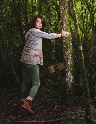 Photographie de Janeuh le survivante dans l'univers de the last of us par le rat graphiste (Janeuh fuie mais s'arrête un instant en s'appuyant sur un arbre dévastée par la perte de son amie)