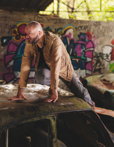 Photographie de Irvin le survivant dans l'univers de the last of us par le rat graphiste (Irvin montant sur une vieille voiture abandonnée)