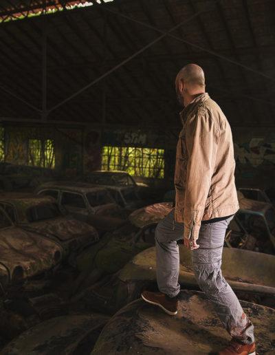 Photographie de Irvin le survivant dans l'univers de the last of us par le rat graphiste (Irvin debout sur une vieille voiture abandonnée)