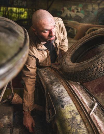 Photographie de Irvin le survivant dans l'univers de the last of us par le rat graphiste (Irvin récupère un vieux marteaux dans une carcasse de voiture)